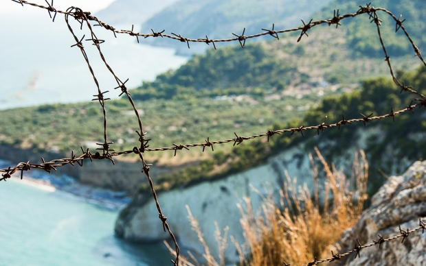 Barbed wire picture with Mediterranean panorama background
